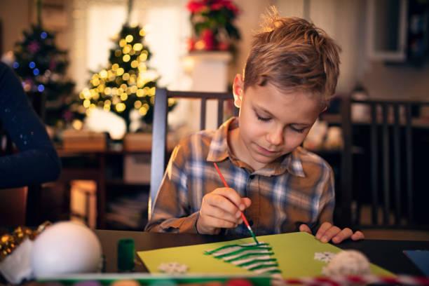 kleine junge malerei weihnachtskarte - winterdeko basteln stock-fotos und bilder