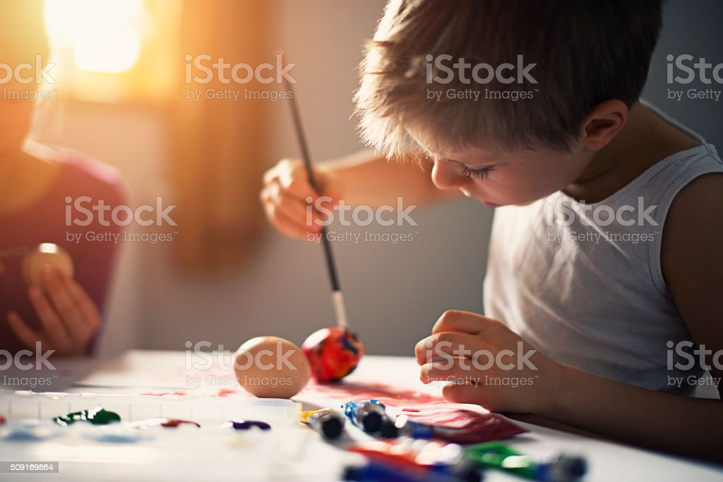 Little boy painting easter eggs stock photo