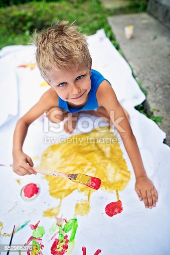 istock Little boy painting outdoors on big paper 682965376