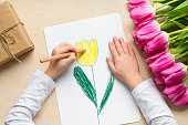 istock Little boy paints greeting card for Mom on Mother's Day or 8 March. Top view 1059944458