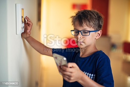 Little boy pairing smartphone with smart home system. Nikon D850