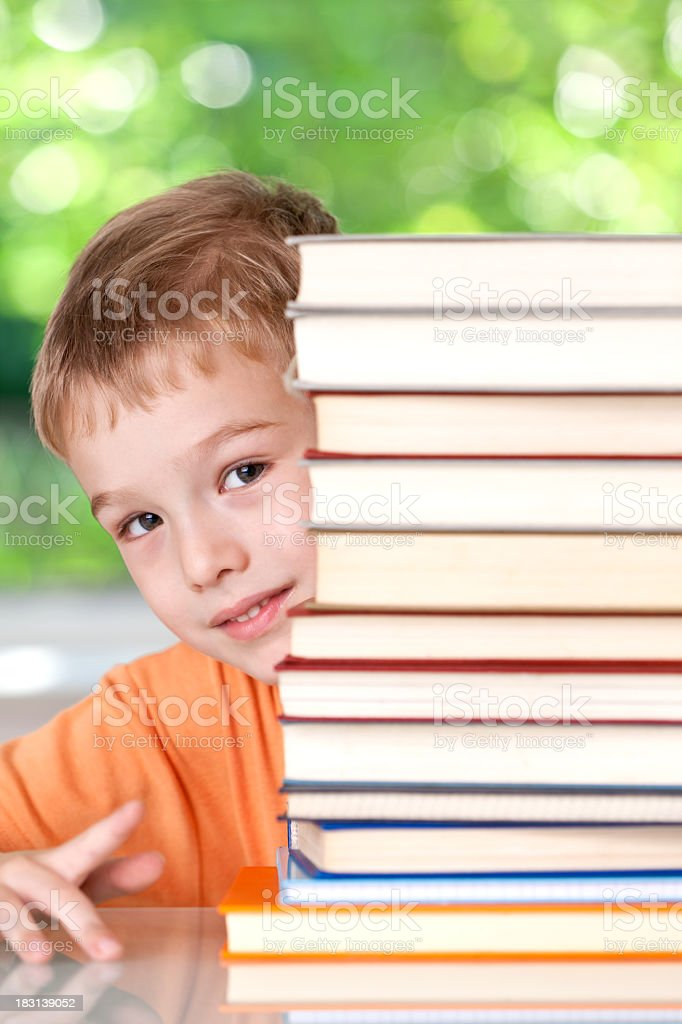 Little boy peeking behind the stack of books royalty-free stock photo