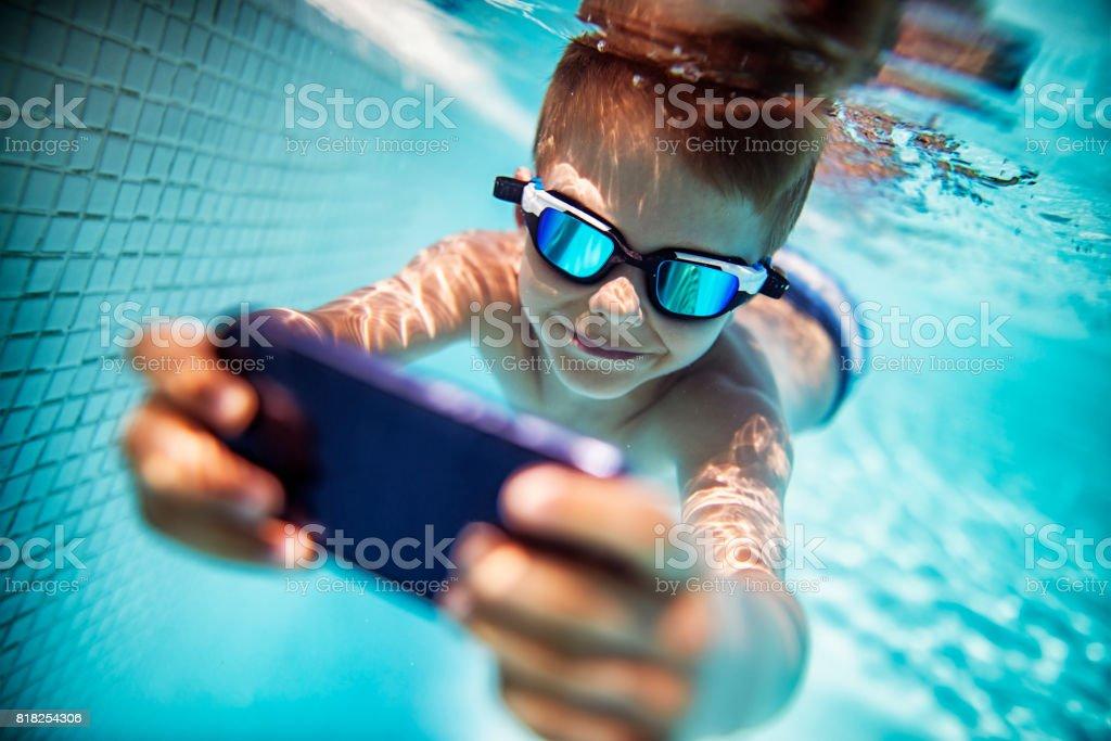Little boy photographing underwater stock photo
