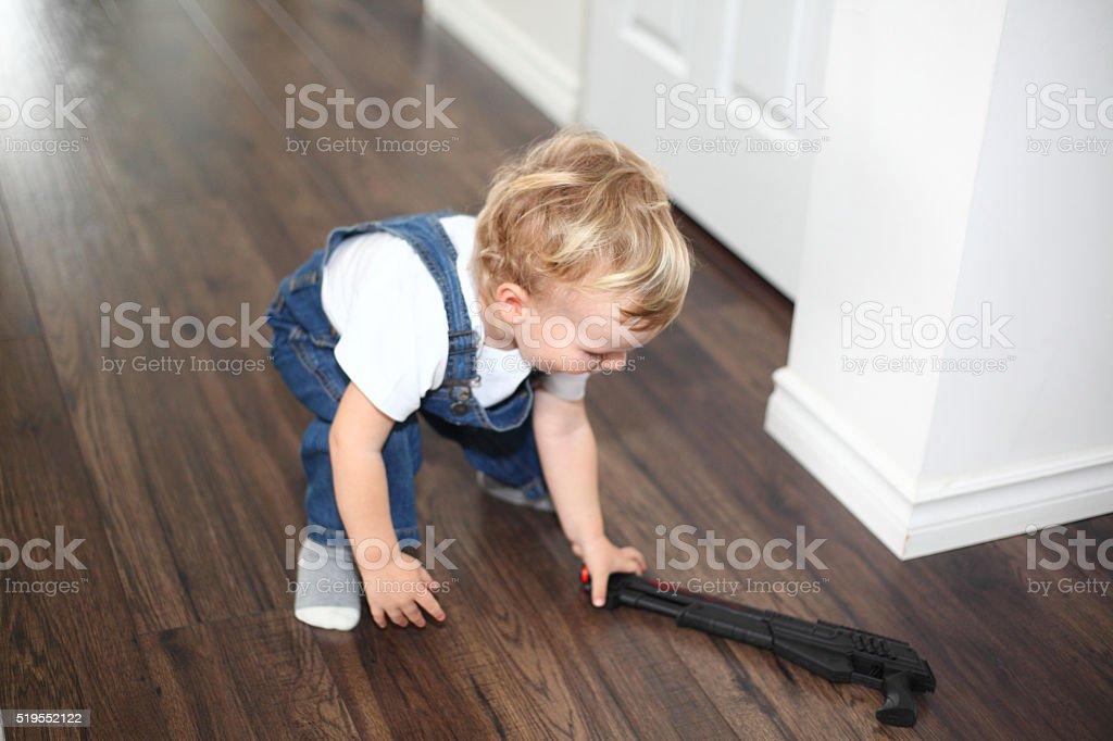 Little boy picking up a gun stock photo