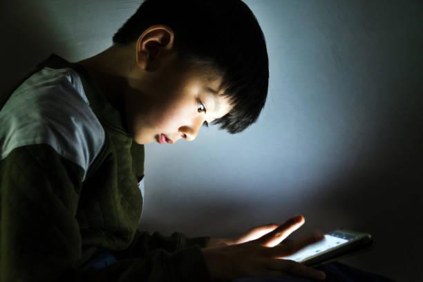 Kleiner Junge Spiel Handy nachts – Foto