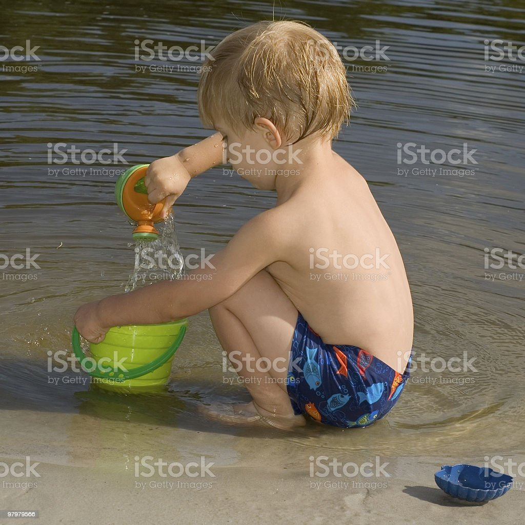 little boy play on the river bank royalty-free stock photo