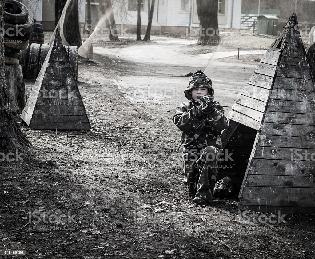 Little boy player with gun during lasertag game. stock photo