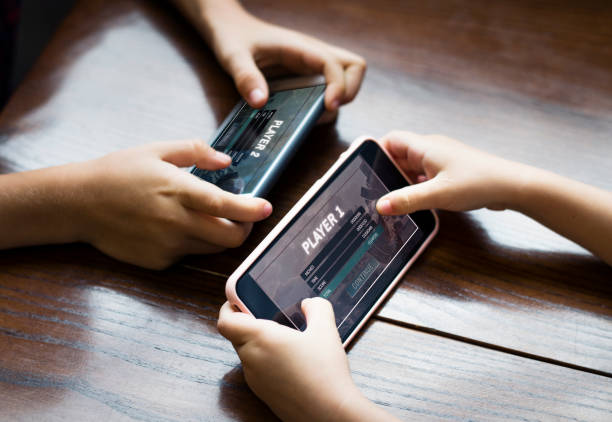 Little boy playing a mobile game against his sister stock photo