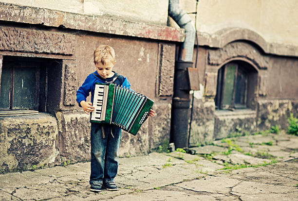 little boy playing accordion - disinherit stock pictures, royalty-free photos & images