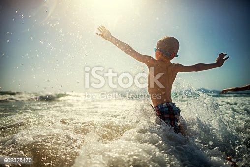 Little boy having fun splashing in sea waves. Sunny day of summer vacations.