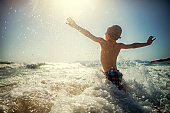 Little boy having fun splashing in sea waves. Sunny day of summer vacations.