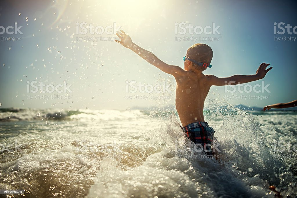 Little boy playing and splashing in sea waves stock photo