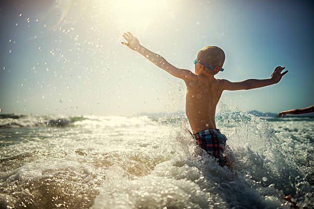 little boy playing and splashing in sea waves - nuoto mare foto e immagini stock
