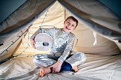Little boy dressed as astronaut playing in his tent. The boy is smiling at the camera.\nNikon D850