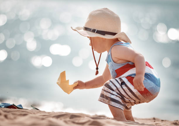little boy playing at the beach in straw hat stock photo