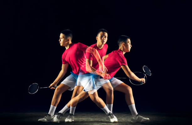 little boy playing badminton isolated on black studio background - badminton sport stock pictures, royalty-free photos & images