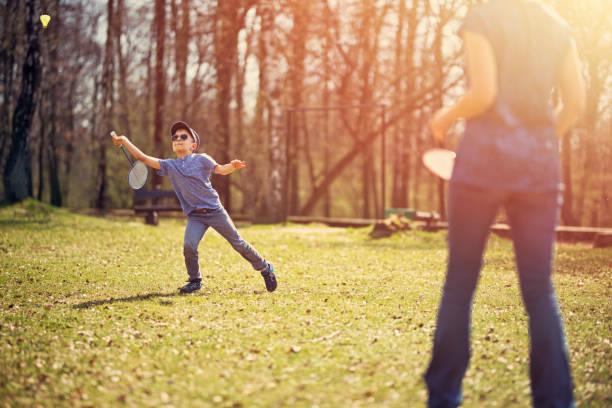 little boy playing badminton with his mother - mãe criança brincar relva efeito de refração de luz imagens e fotografias de stock