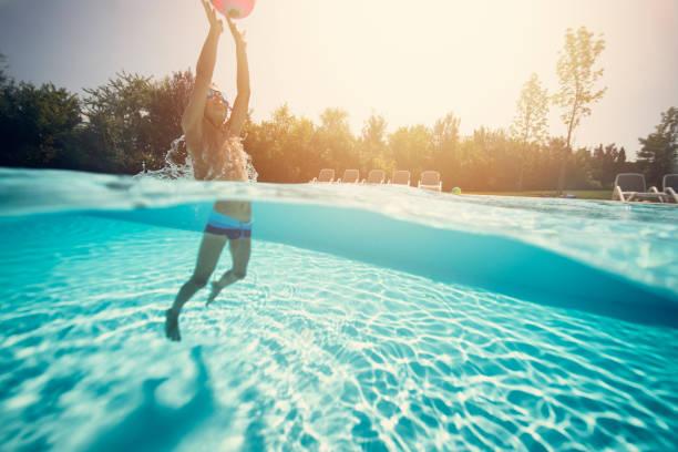 little boy playing ball in swimming pool - jump pool, swimmer imagens e fotografias de stock