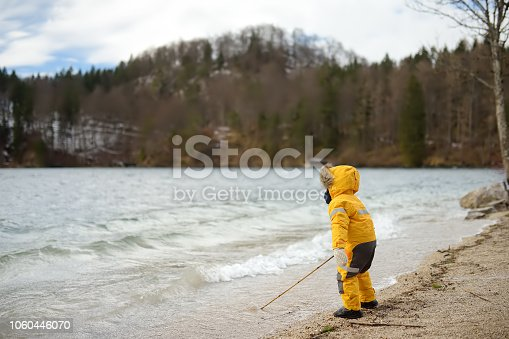 Little boy playing by Alpsee lake, located near Hohenschwangau and Neuschwanstein Castles. Bavaria, Germany. Child walk in windy and cold day