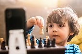 istock Little boy playing chess with a friend using teleconferencing 1284809354