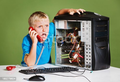 istock Little boy playing computer technician with broken pc and phone 185279604