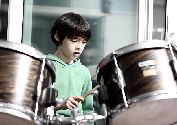 Little boy playing drumkit stock photo