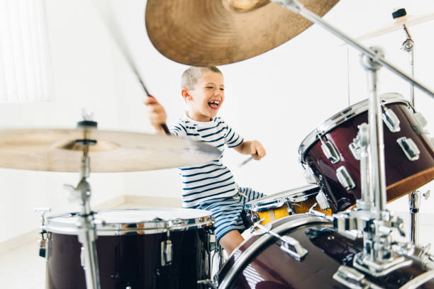 Little boy playing drums Determined little boy learning how to play drums drum kit stock pictures, royalty-free photos & images