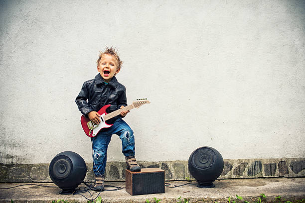 Little boy playing electric guitar stock photo