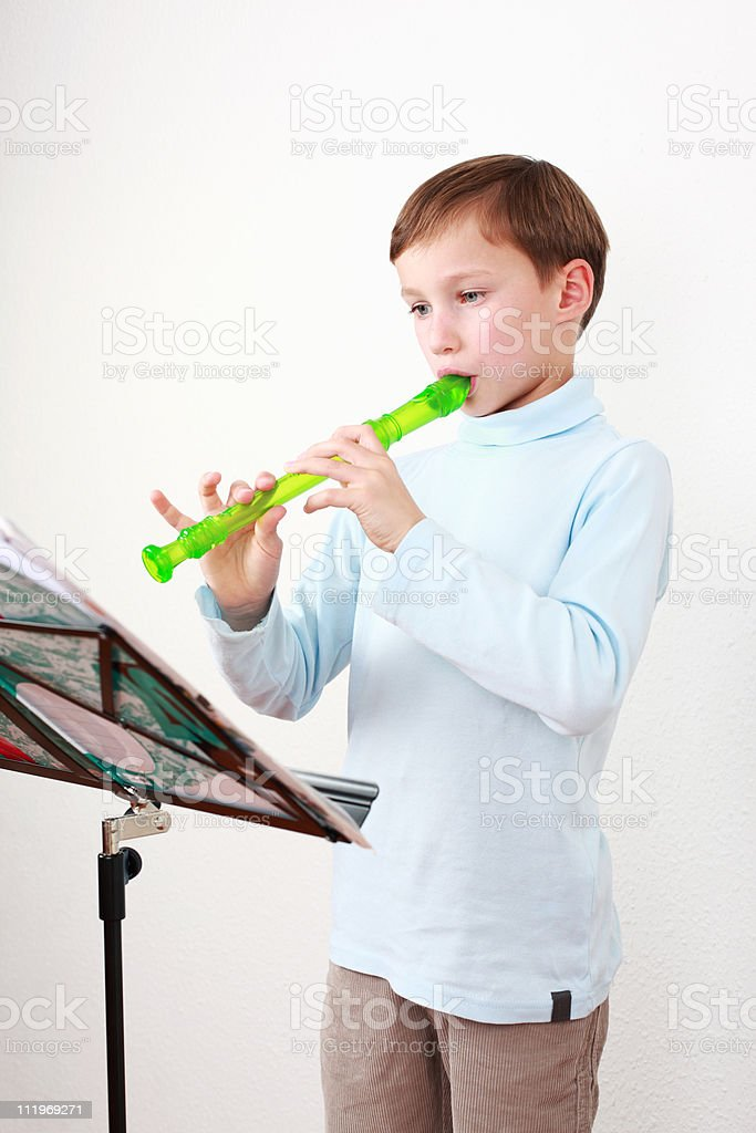 Little boy playing flute stock photo