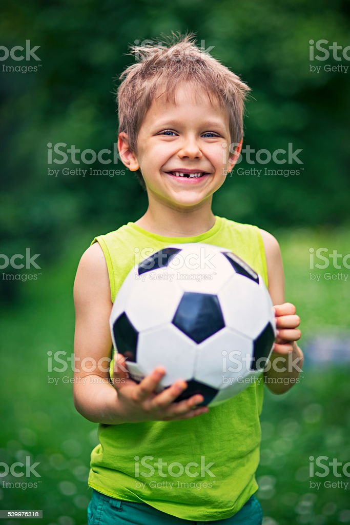 Little boy playing football in the garden stock photo