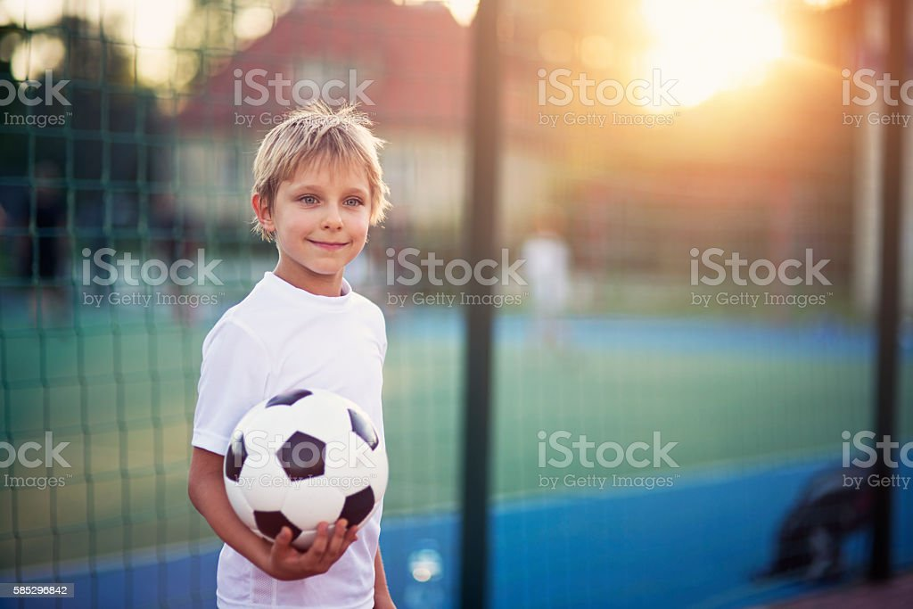 Little boy playing football in the schoolyard stock photo