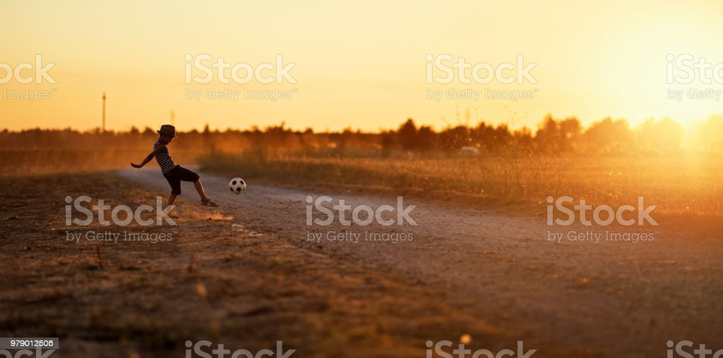 Little boy playing football on dirt road royalty-free stock photo