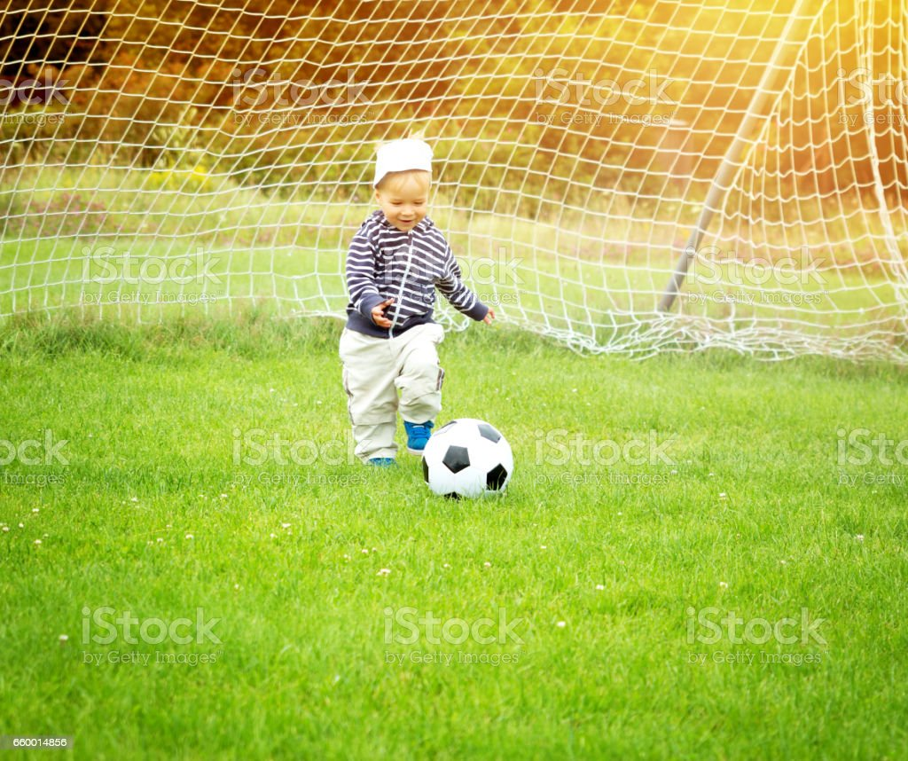 Little boy playing football on the field with gates stock photo