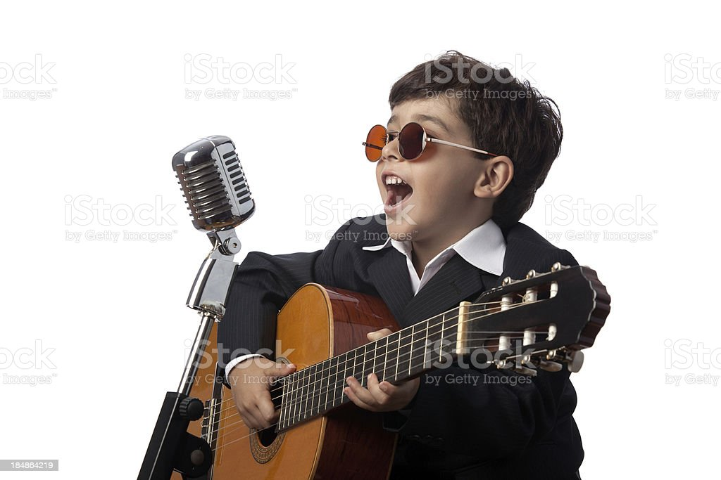 Little boy playing guitar in front of old fashioned microphone royalty-free stock photo
