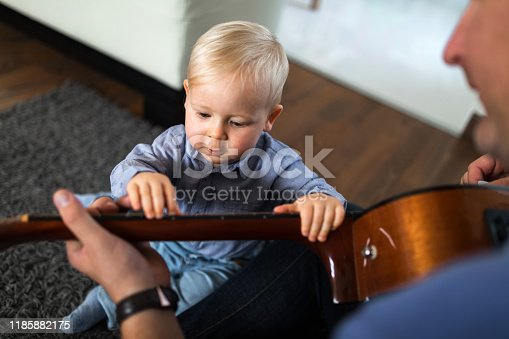 649431568 istock photo Little boy playing guitar with his father 1185882175