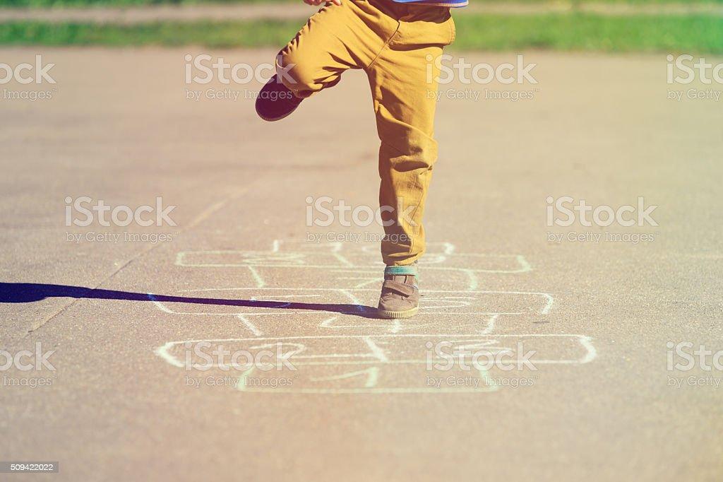 Kleiner Junge spielt auf Spielplatz Himmel-und-Hölle-Spiel - Lizenzfrei Aktiver Lebensstil Stock-Foto