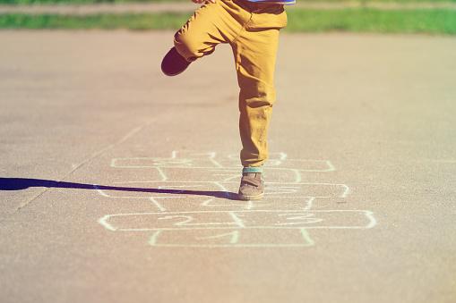 Kleiner Junge Spielt Auf Spielplatz Himmelundhöllespiel Stockfoto und mehr Bilder von Aktiver Lebensstil
