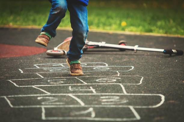 kleiner junge spielt auf spielplatz himmel-und-hölle-spiel - himmel und hölle spiel stock-fotos und bilder