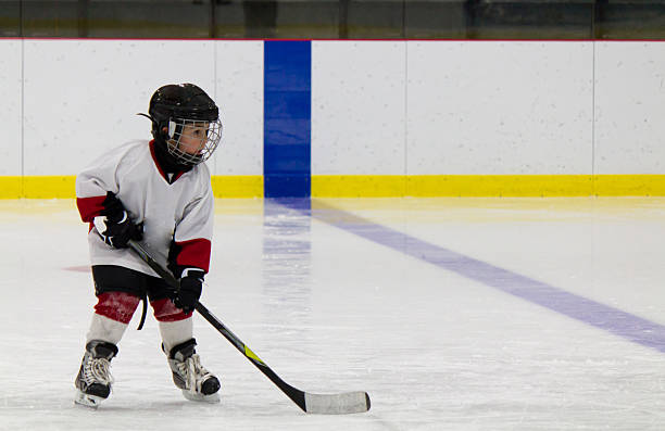 A little boy playing ice hockey on the rink stock photo