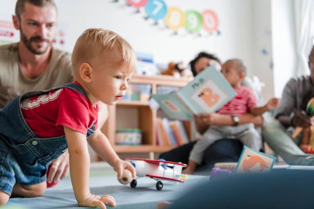 kleiner junge spielt in einem klassenzimmer - 2 3 jahre stock-fotos und bilder