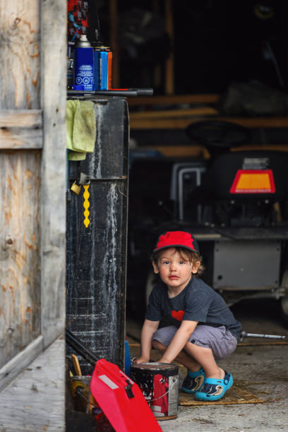 Little boy playing in a garage stock photo