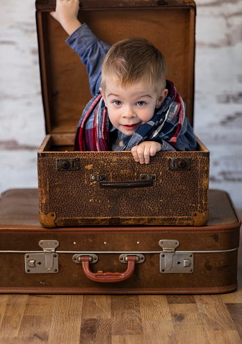 little boy playing in a suitcase, concept childhood and travel