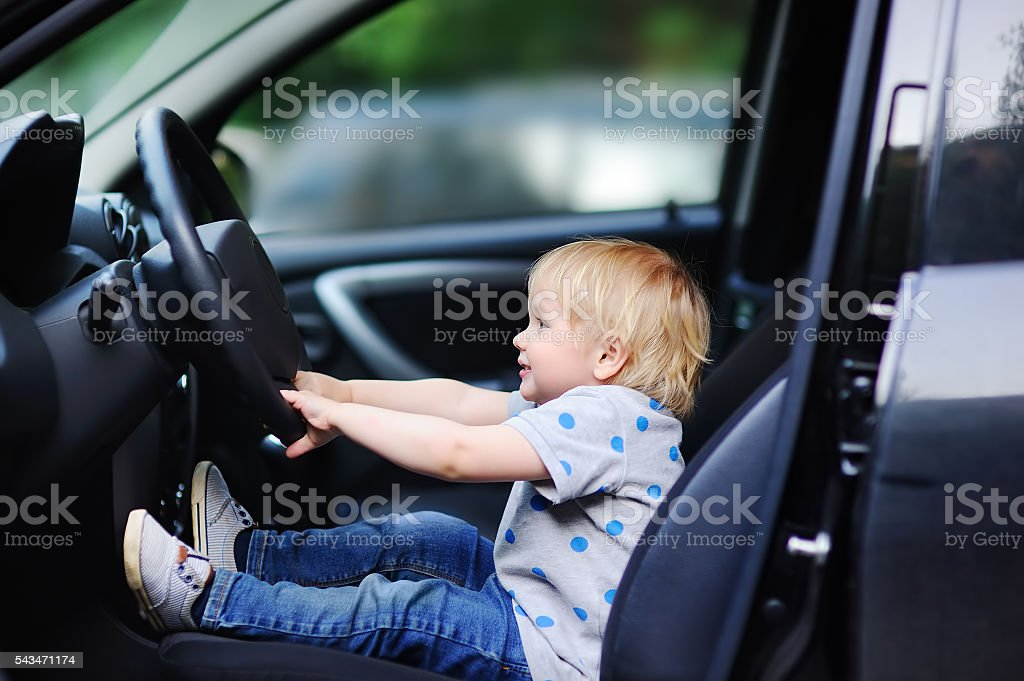 Little boy playing in fathers car stock photo