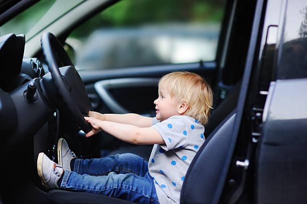 little boy playing in fathers car - autos für fahranfänger stock-fotos und bilder