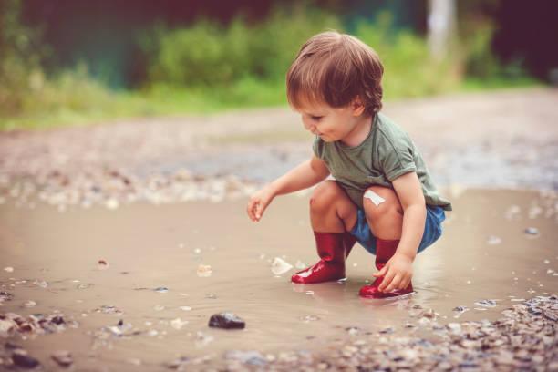 Kleiner Junge, der an einem regnerischen Tag in Pfütze spielt – Foto