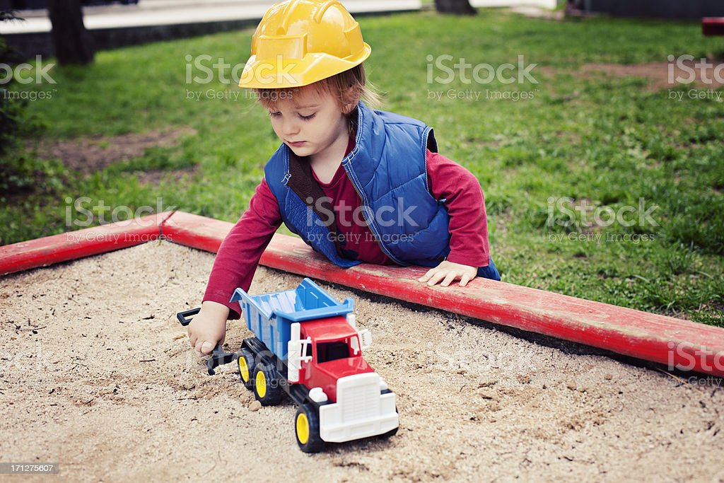 Little Boy Playing In Sandbox stock photo