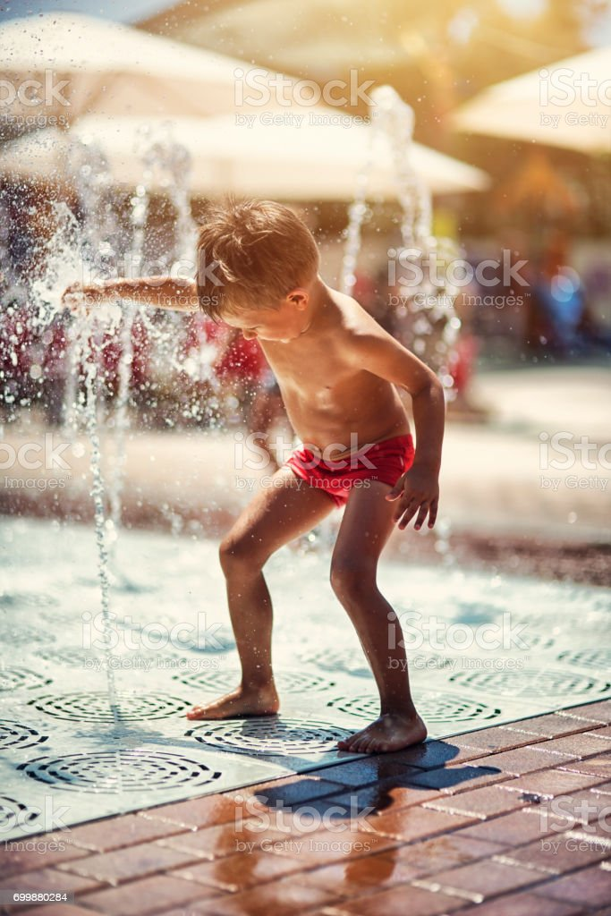 Little boy playing in splash pool fountains. stock photo