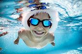 Little boy wearing Santa hat having fun swimming underwater during summer Christmas. \nNikon D810