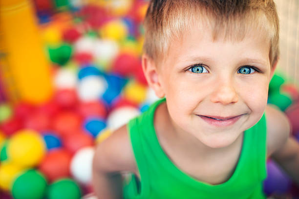 Little boy playing in the ball pool stock photo