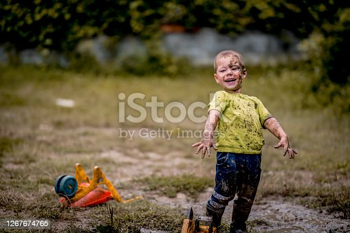 istock Little boy playing in the mud. 1267674765